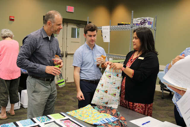 A woman is showing two men a sheet of colorful fabric. They are listening to her intently as she talks. They are in a library.