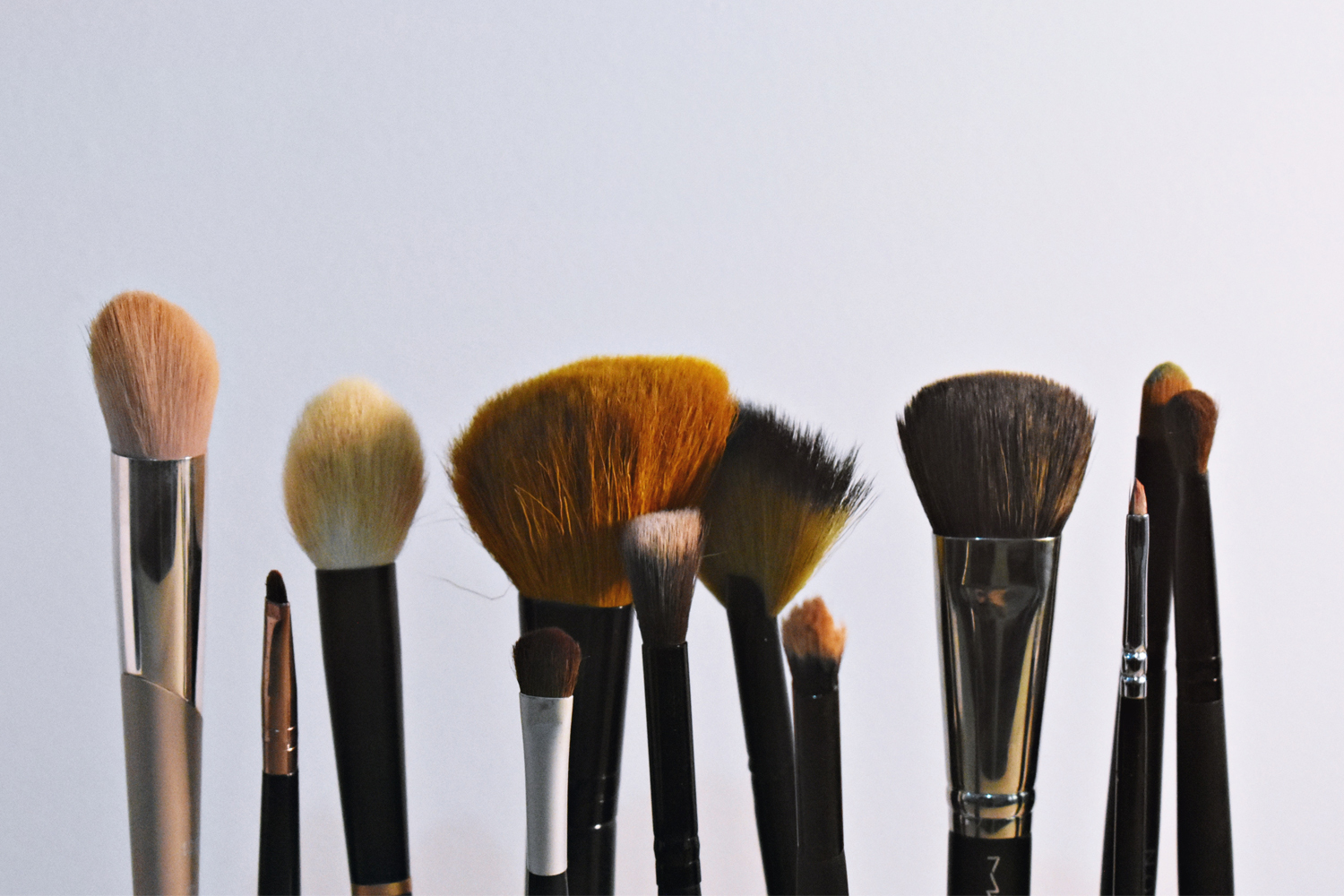 a few makeup brushes on plain background