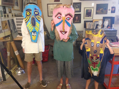 Our grandkids and the masks we painted on palm fronds.