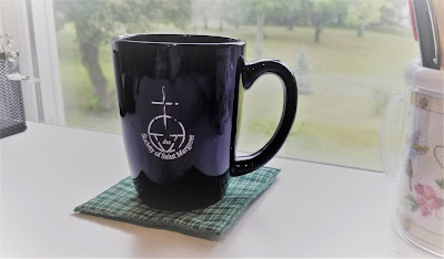 """ginger clove tea in an old blue mug that reads """"Society of St. Margaret"""" on a green quilted coaster on a white desk. Behind the mug is a window with a view of green trees and a rainy, grey day"""