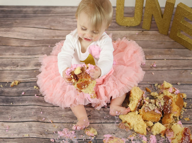photo of messy baby girl cake smash baby holding cake