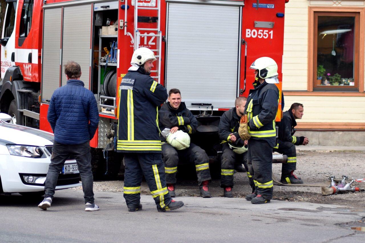 Ugunsdzēsēji atpūšas ugunsgrēka laikā