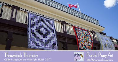 Quilts hang from the Wainwright Hotel during Festival of Quilts, Heritage Park