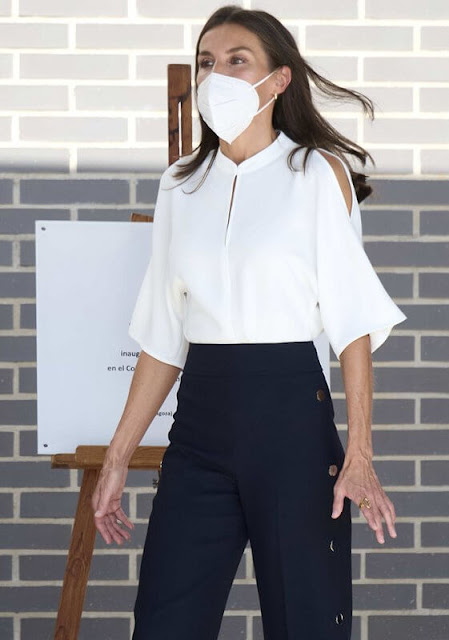 Queen Letizia wore a white shirt by Adolfo Domínguez with buttoned navy Hugo Boss trousers. Castaner espadrille wedges