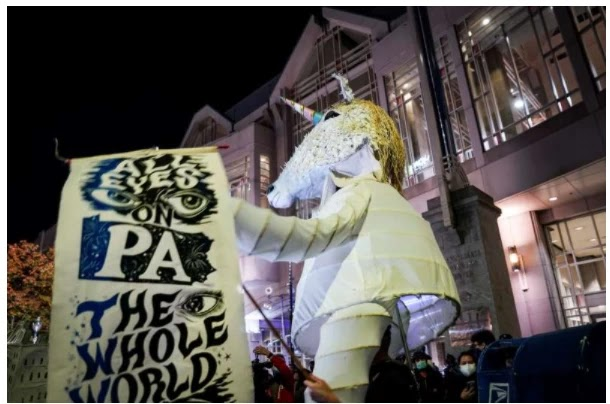 giant anthropomorphic unicorn creature is paraded among demonstrators gathered outside the Philadelphia Convention Center three days after the presidential election polls closed as they await tabulation results, Friday, Nov. 6, 2020, in Philadelphia.