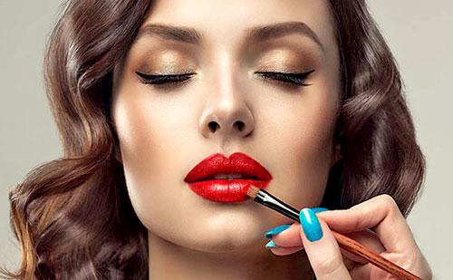 Mujer pintándose los labios de rojo