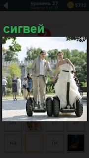 Жених и невеста в белом платье на сигвее раскатывают по парку, держась за руки