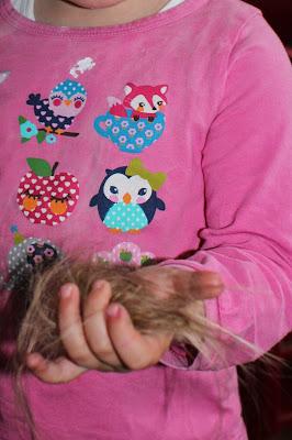 Kind hält abgeschnittene Haare in der Hand