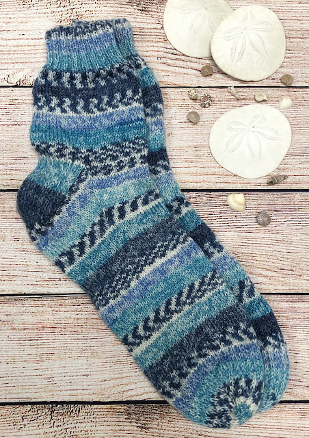 Socks knitted with DROPS Fabel Shoreline with reinforced heels and toes next to sand dollars and seashells