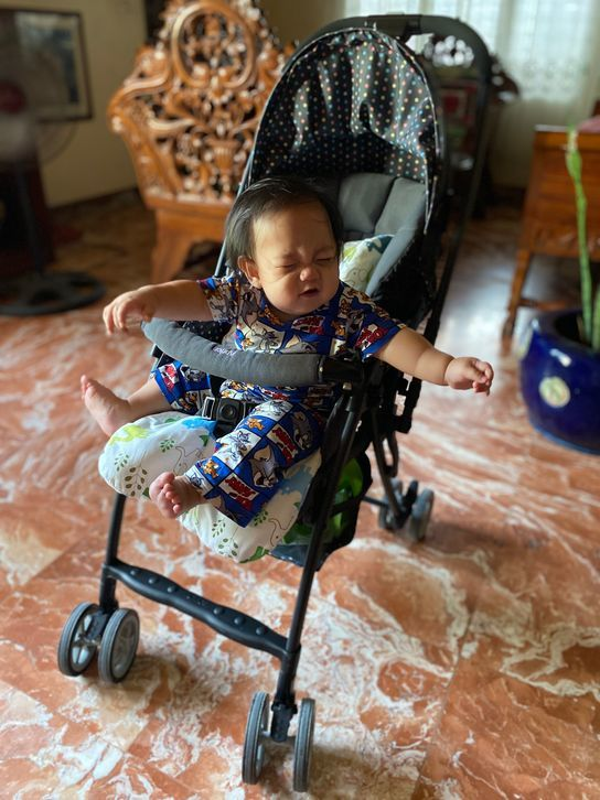 Our baby happily smiling while on his Aprica Baby Stroller