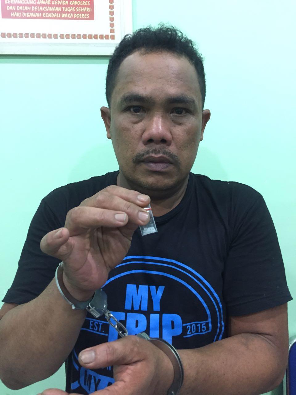Tersangka Sangkot Simamora memperlihatkan barang bukti paket sabu.