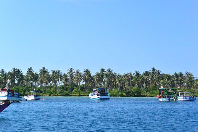 Kapal-kapal mengantarkan wisatawan tur laut