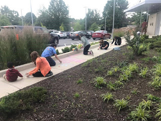Teens chalking text and pictures on the walkway of Gaithersburg Library.