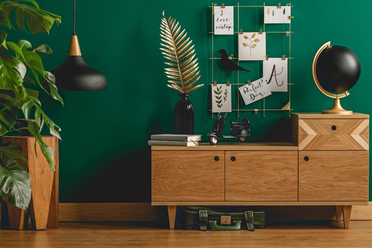 Pared en tono verde oscuro con muebles de madera