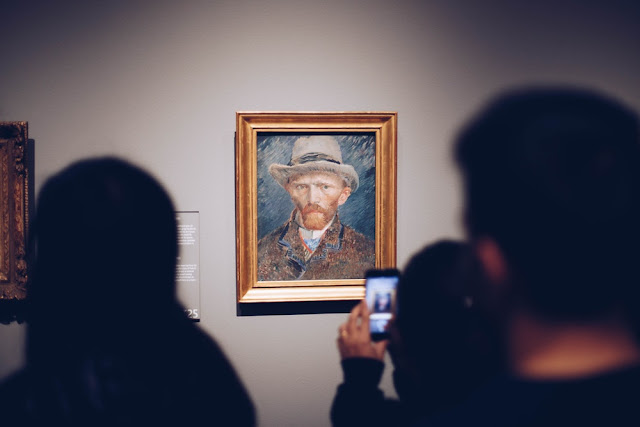 People looking at a portrait of Van Gogh by Van Gogh. I think he has his ear on in this one