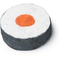A circular white bath bomb with a black outer ring and a circular orange inner circle on a bright background
