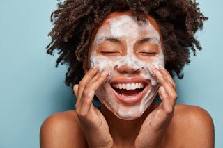 mulher negra passando produto na pele do rosto