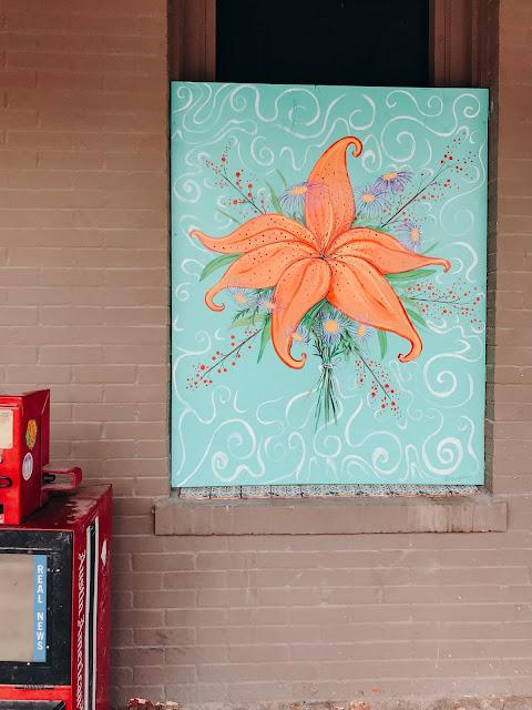 Orange flower painting sitting in window next to newspaper stand.