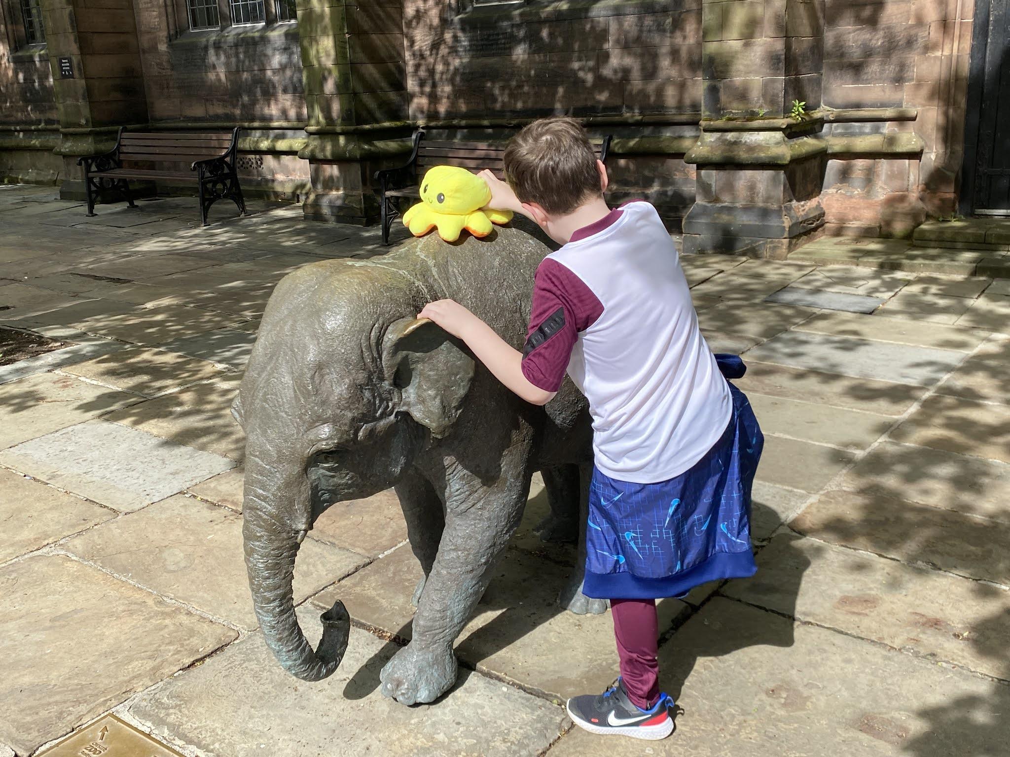 boy climbing an elephant statue