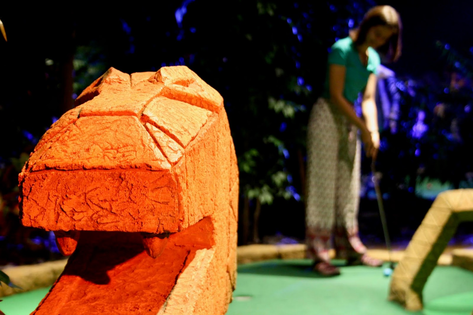 A close up of a snake head decorating one of Treetop's golf holes, with Abbey taking a shot in the background