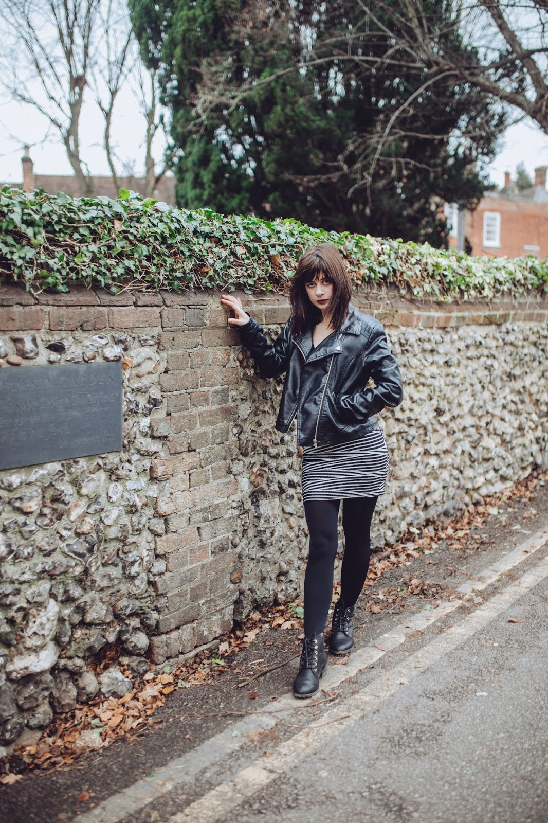 Laura is standing in front of a brick wall. She is wearing a leather jacket and a pencil skirt