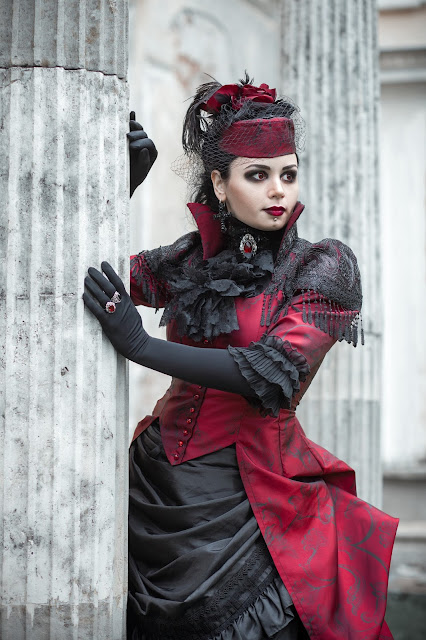 Woman wearing Black and Red Gothic Victorian dress with ruby jewelry. Steamgoth fashion.