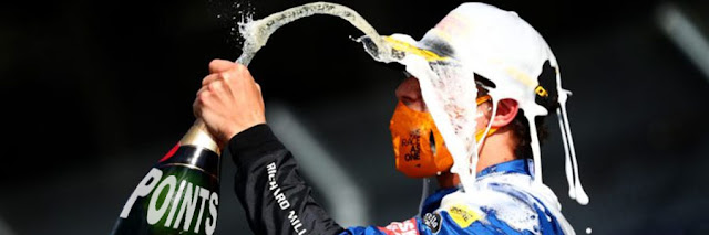 """A driver spraying themselves in the face with a champagne bottle marked """"POINTS"""""""