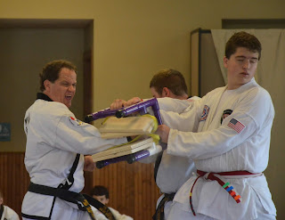 Kyle F, martial arts black belt, breaking board with a knifehand strike