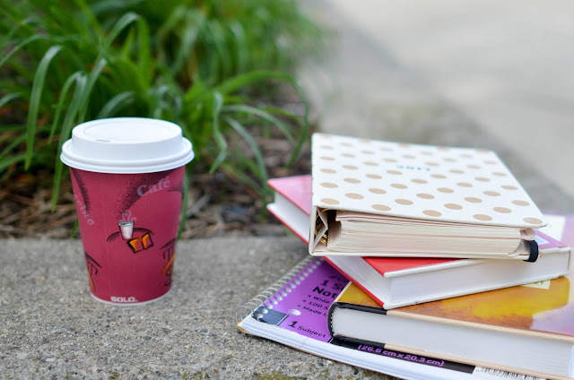 A pile of books on the ground next to a red disposable coffee cup