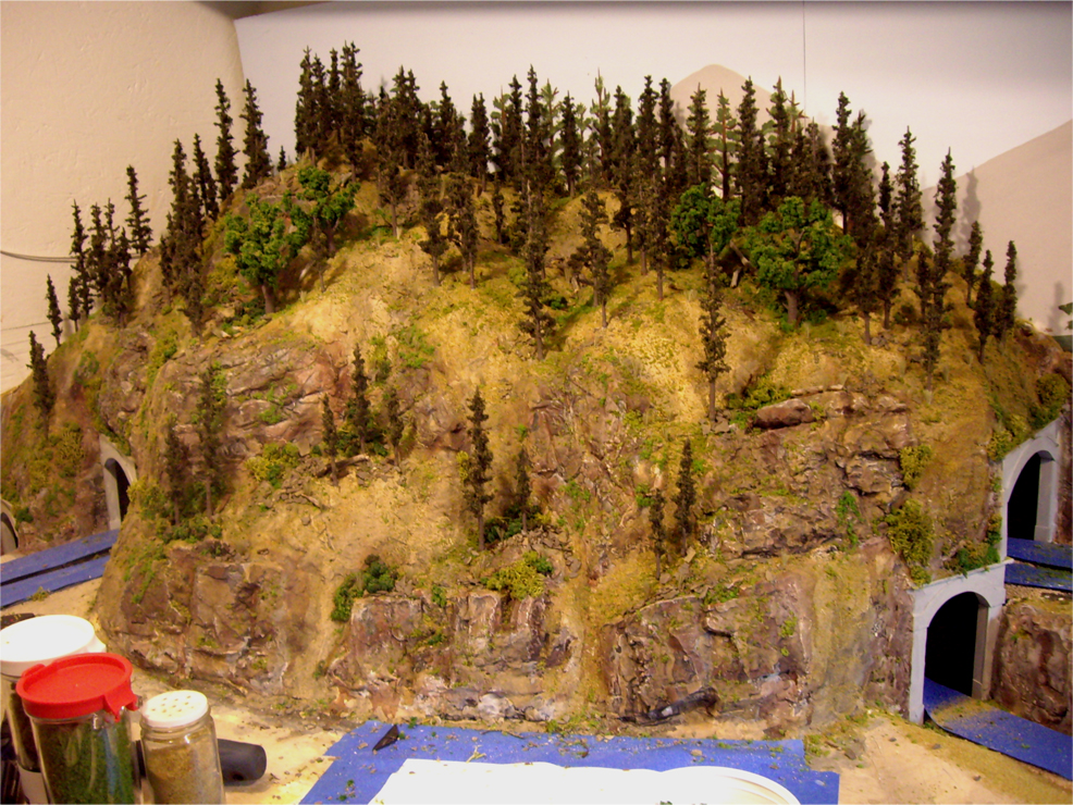Mountain made from plaster covered with various ground foam, trees, and talus to create a forest scene