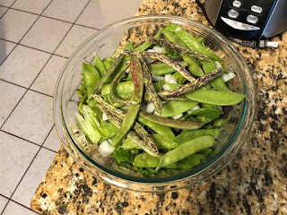 Glass bowl on countertop filled with salad topped with beans and peas