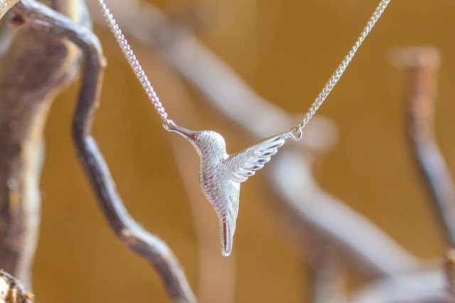 Silver hummingbird necklace against gold background and twigs