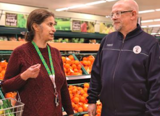 A caucasian woman with brown hair carrying a basket wearing a green sunflower printed lanyard speaking to a member of staff inside a supermarket.