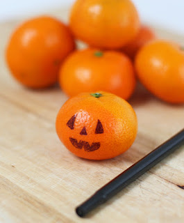 Draw jack-o-lantern faces on clementines or mandarins
