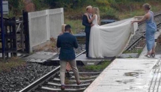 Bride and groom pose for wedding photos on railway track