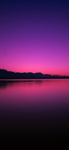 خلفية انعكاس شفق الغروب فوق مياه البحيرة الهادئة