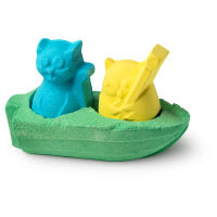 A light blue green boat shaped bath bomb with a purple cat and a yellow owl attached on a bright background