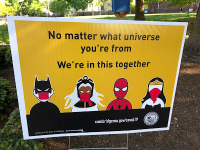 "Batman, Storm, Spider-Man and Wonder Women wearing face masks below the words ""No matter what universe you're from we're in this together"""