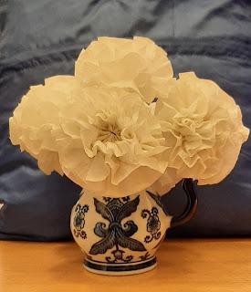 Na beżowym blacie stołu stoi biały wazon w niebieskie kwiaty. W wazonie stoją białe kwiaty. Za wazonem niebieskie tło.