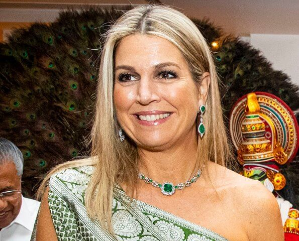 Queen Maxima wore a pale green one shoulder patterned dress which she coordinated with a bright emerald green clutch
