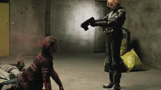 Dredd film still Judge Anderson shooting a perp in the head