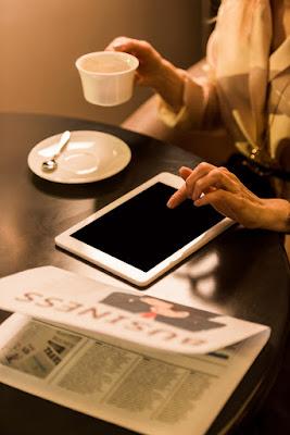 pessoa lendo jornal e tomando café
