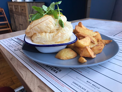 pie and chips on a blue plate on top of a menu on a wooden table