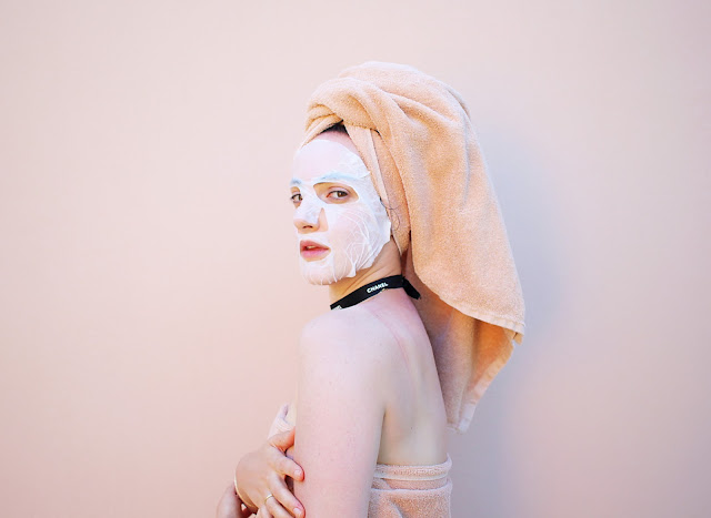 כותבת הכתבה עם מסכת הבד של דרמגלאם על פניה כשהיא עטופה במגבת.