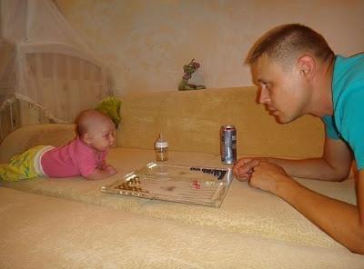 Witziger Vater und Baby spielen zusammen Brettspiel