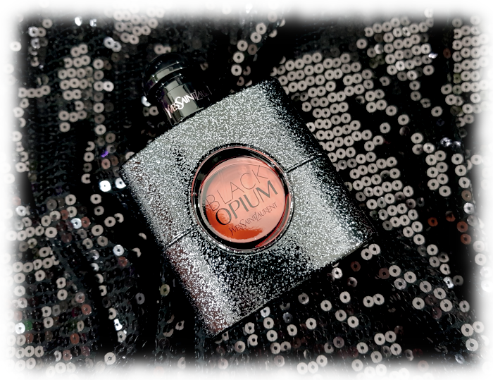 Black Opium bottle on black sequinned background