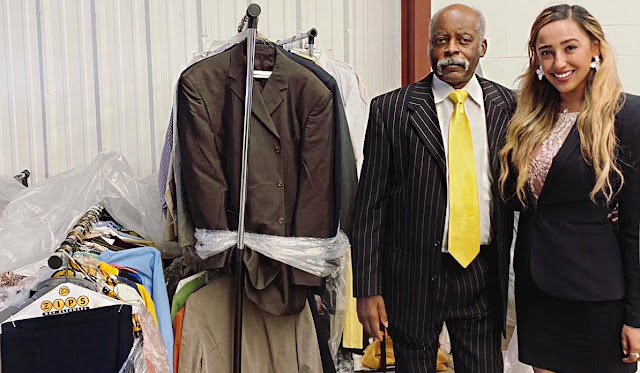 Retired U.S. Army Sergeant Prince Rawlings and first-year USU medical student & volunteer Zoya Mahajan standing with some of the donated suits.