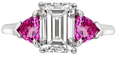 2.05 carat emerald-cut diamond engagement ring with pink sapphire side stones. Via Diamonds in the Library.