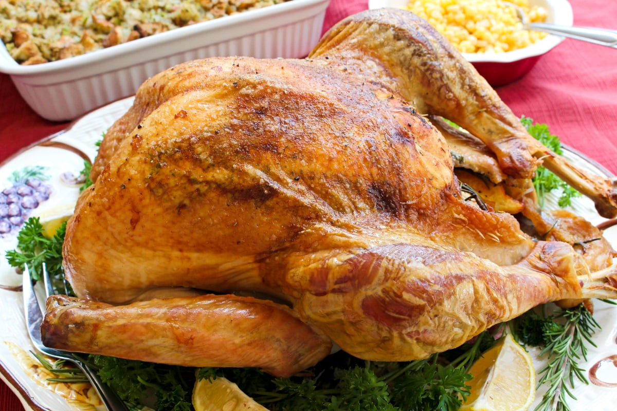 This Easy Oven Roasted Turkey recipe makes the best juicy, tender, golden brown turkey that is perfect for the holidays.  You will want to use this recipe year after year! #thanksgiving #turkey
