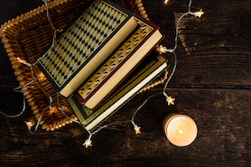 January reads vintage books in a wicker basket surrounded by fairy lights